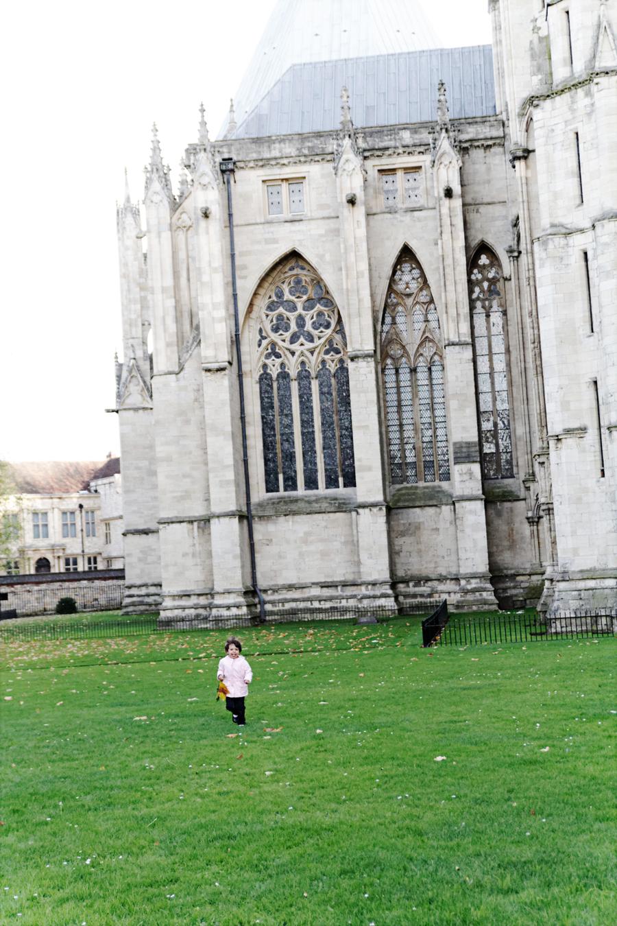 Lily brincando no parque à sombra da catedral.